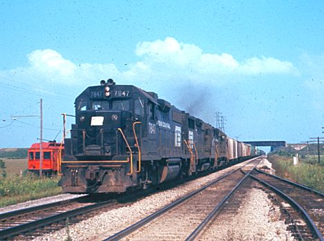 Penn Central 7847, leads a westbound train through Delta, Ohio on the main line going towards Elkhart and Chicago.  In the background, the Detroit, Toledo & Ironton crosses overhead.  The Wabash Railroad is to the right, out of the photo, and you can also observe an old interurban car to the left.  September, 1972  [Mark Dobronski]