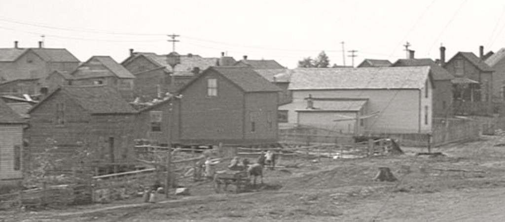 Here we have a view of the adjacent housing which is most likely owned by the mine itself. Some points of interest are; The martin house atop the electric pole.Many structures are on top of piers and do not have foundations. No cars just horses and buggies.  Every yard has a fence and types are varied.