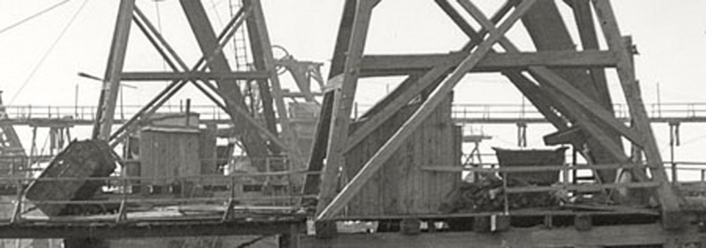 In this closeup view of the head frame, we can see one of the skips tipped up and what appears to be a wagon most likely for tailings.