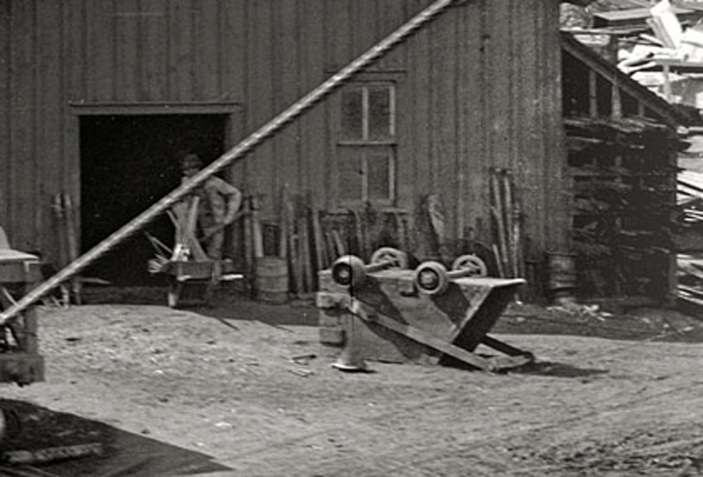 This building appears to be a repair or blacksmith shop. Materials and tools are stacked against the building. A skip is upside down, presumably to be fixed. It appears the ore cars may need repairs to. The car closest is only partially filled while the other two are not.